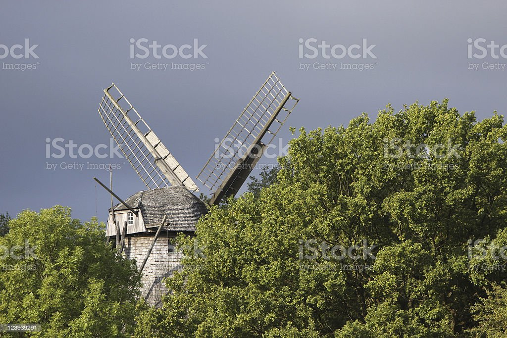 Windmill behind trees royalty-free stock photo