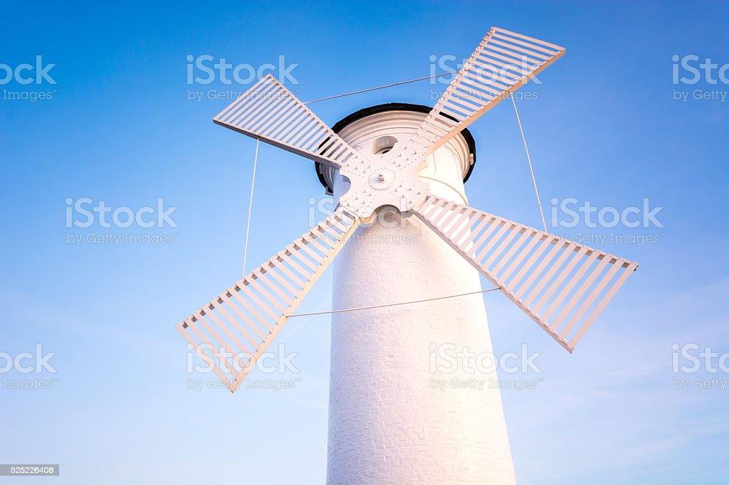 Windmill by the sea on the rocky coast. stock photo