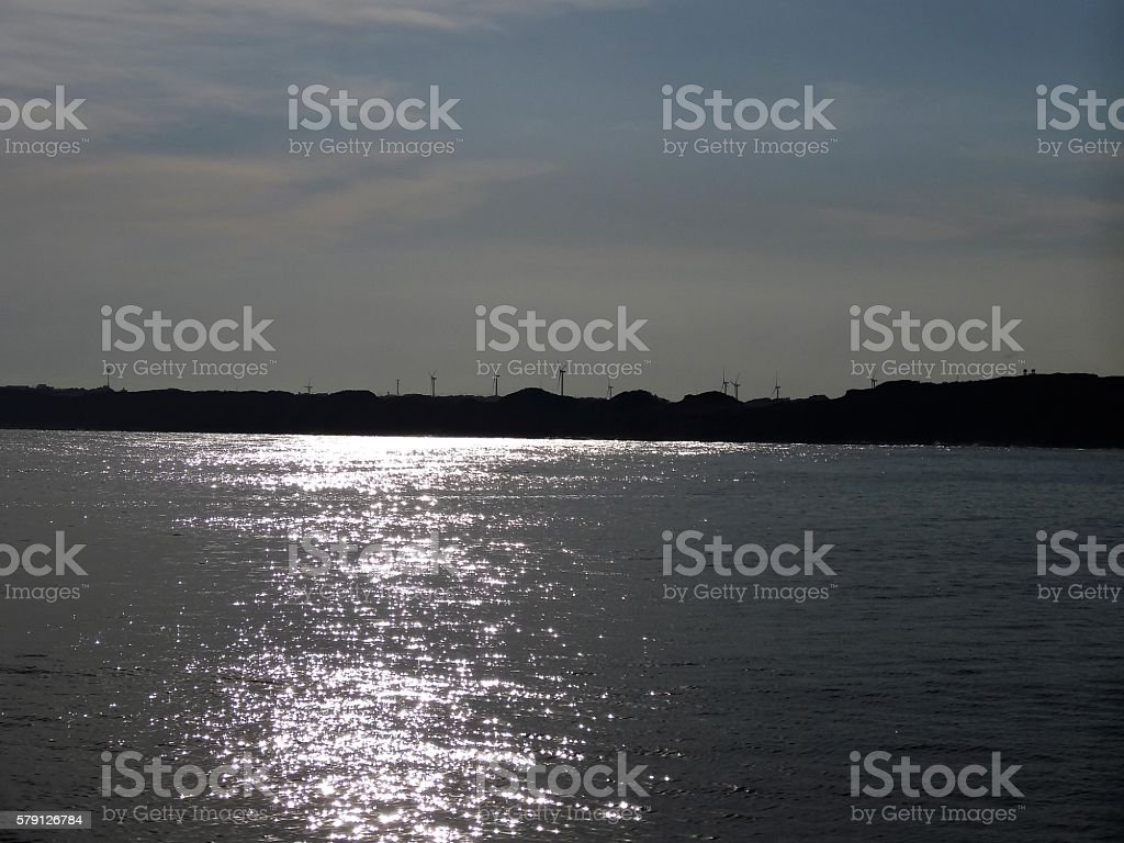 Windmill cluster and the silhouette of the beach stock photo