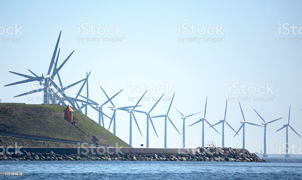 A windmill farm on the hill by water royalty-free stock photo