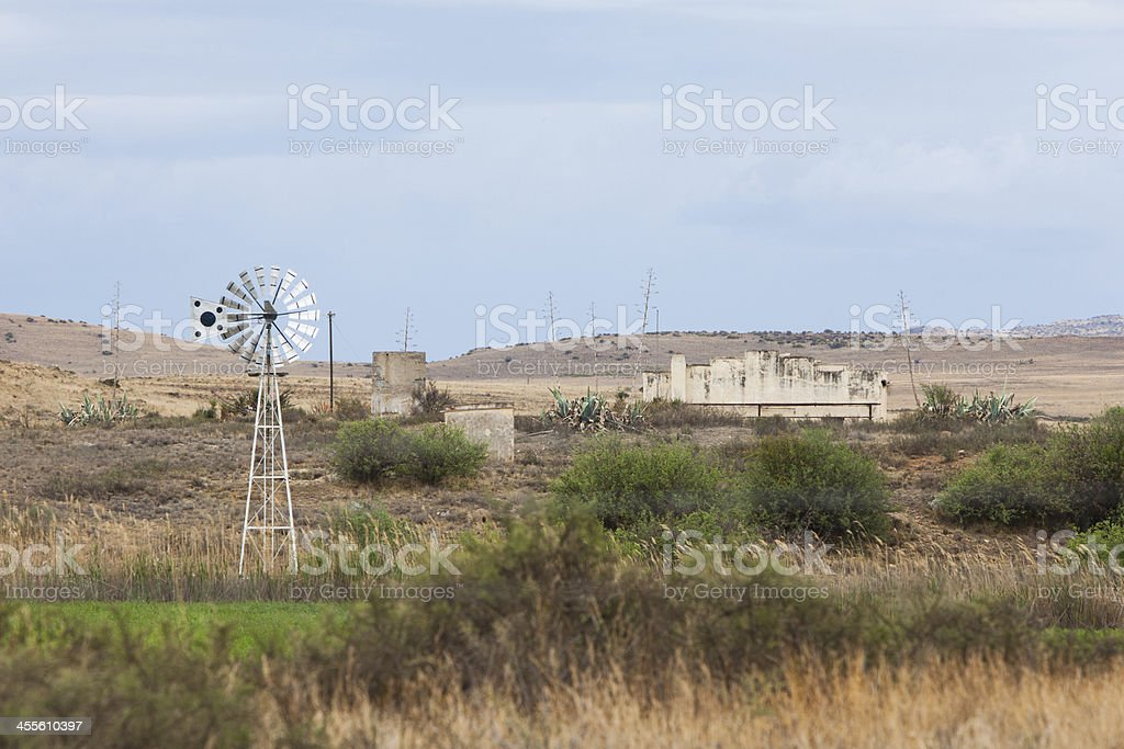 Windmill on a farm with demolished building stock photo