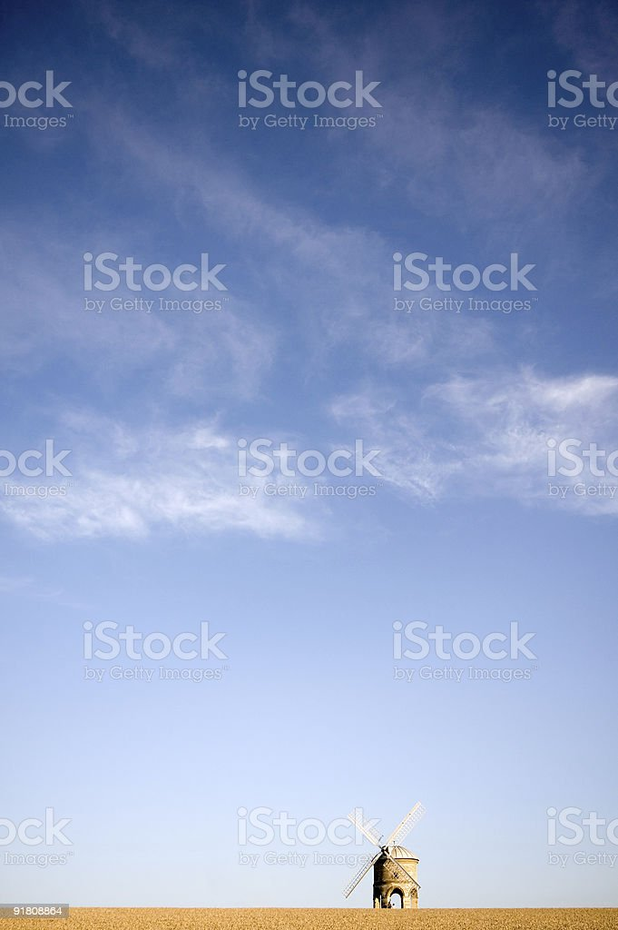 Windmill on a hilltop with blue skies stock photo