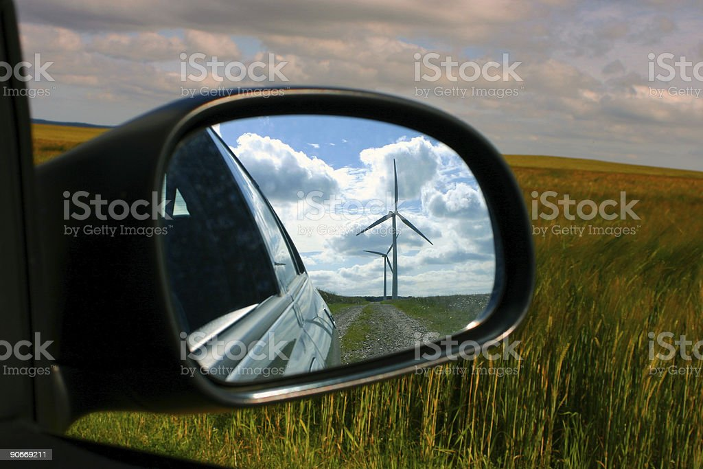 Windmill reflected in car wing mirror with view of fields. royalty-free stock photo