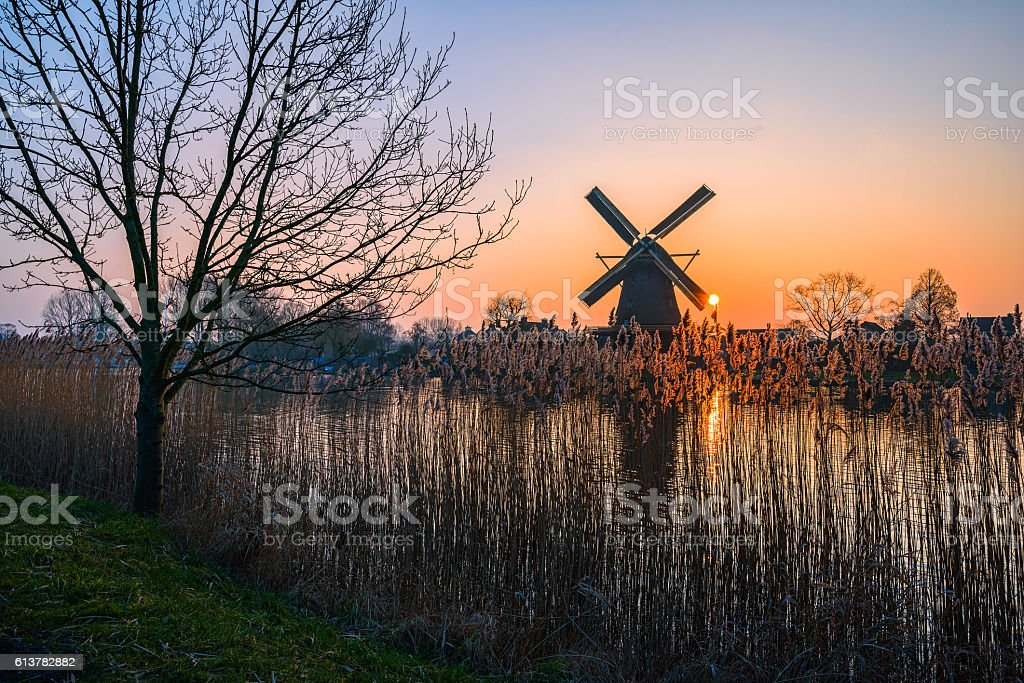 Windmill silhouette behind the lake at sunset stock photo