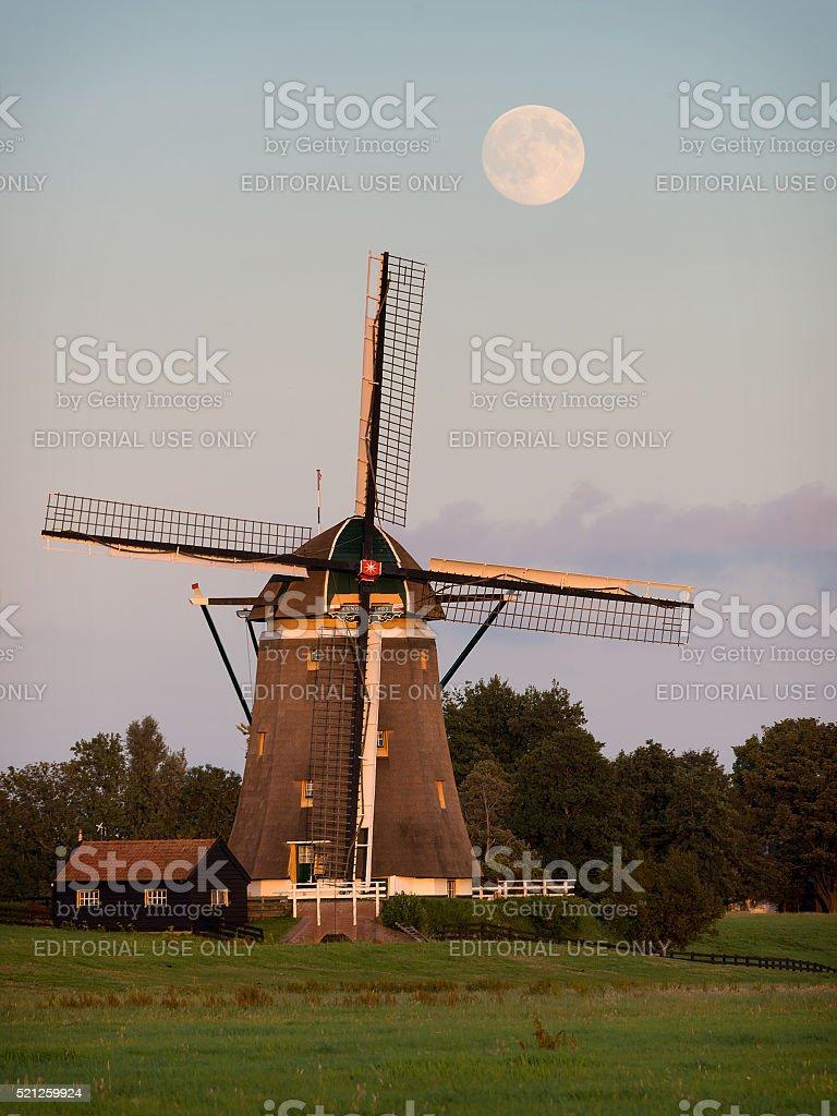 Windmill under a full moon stock photo
