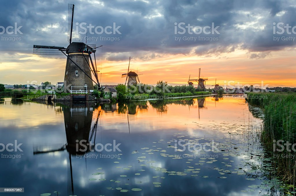 Windmills along a Canal under Cloudy Sky at Sunset stock photo