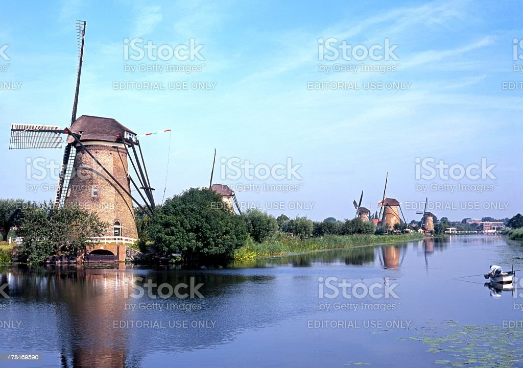 Windmills alongside river, Kinderdijk. stock photo