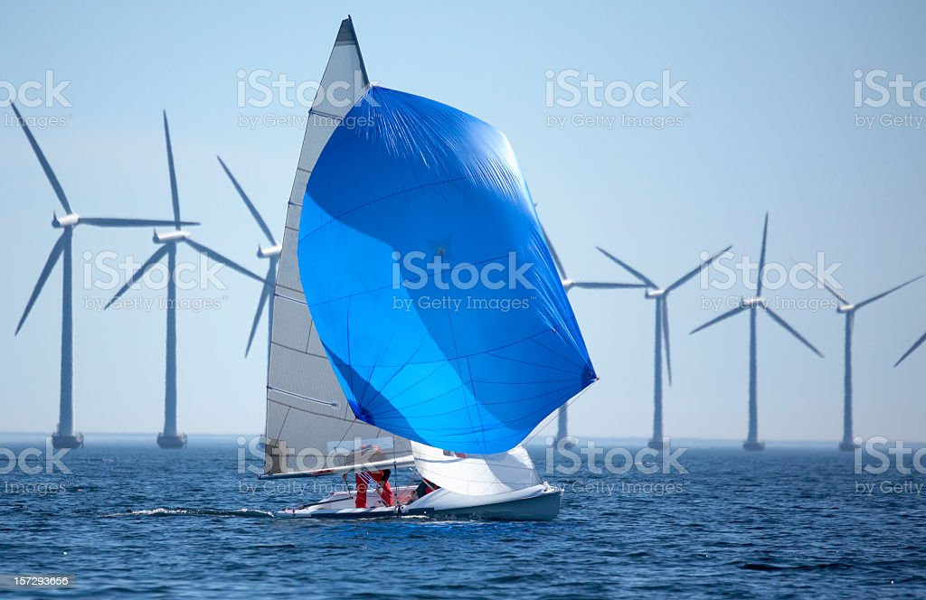 Windmills and a sailboat in the middle of the sea stock photo