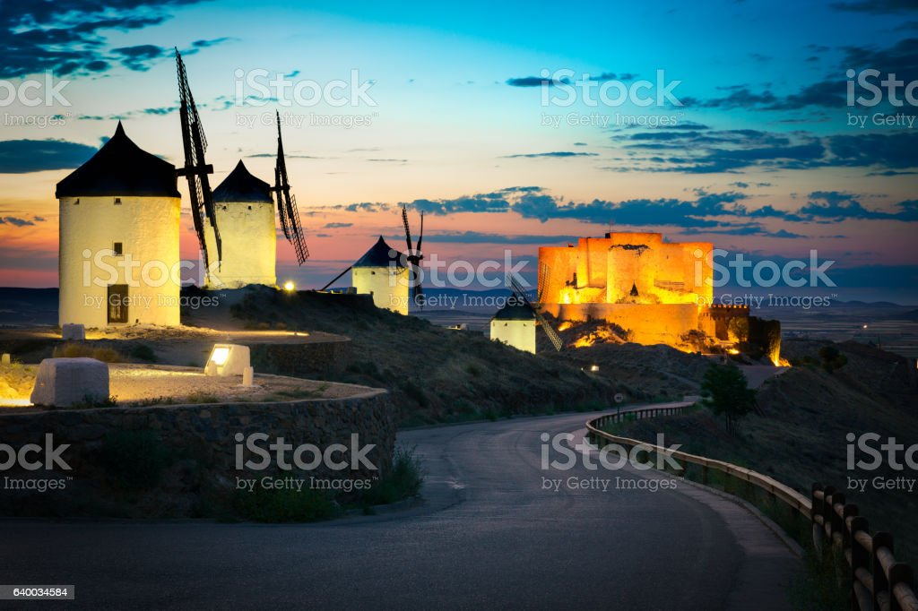 Windmills and castle after sunset, Consuegra, Castile-La Mancha, Spain stock photo