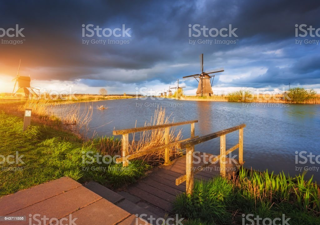 Windmills at sunset in Kinderdijk, Netherlands. Rustic landscape with wooden pier against amazing dutch windmills near the canals and cloudy blue sky reflected in water in the evening. Overcast stock photo