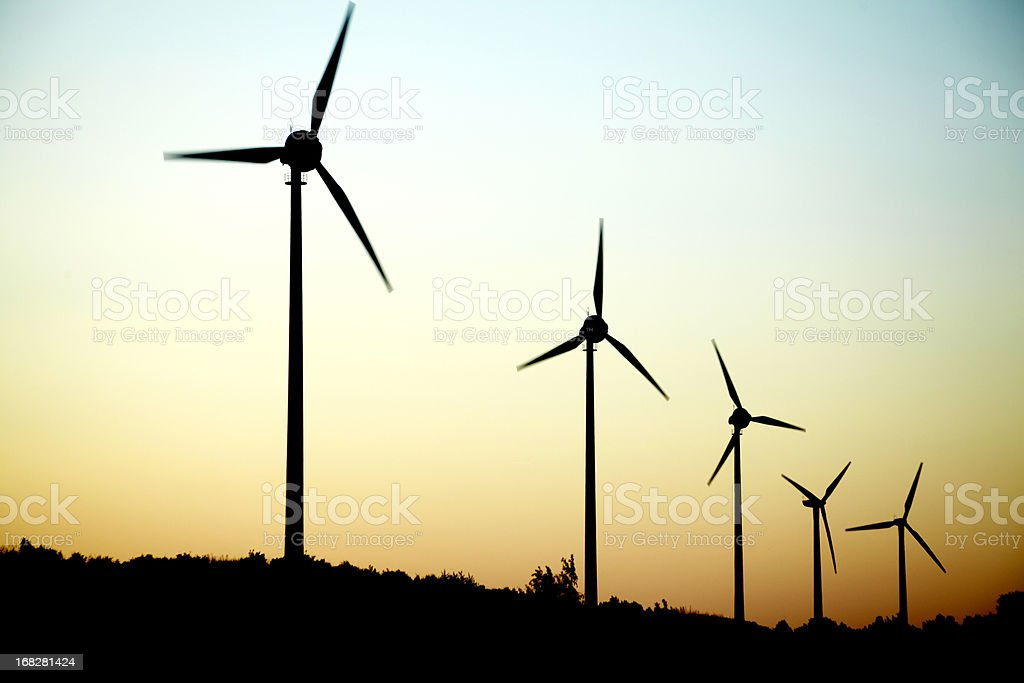Windmills in a row at dusk stock photo