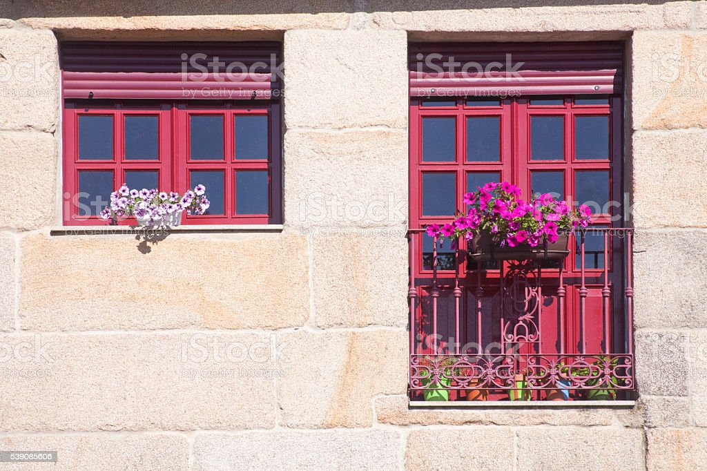 Window and balcony with flower pots stone facade. stock photo