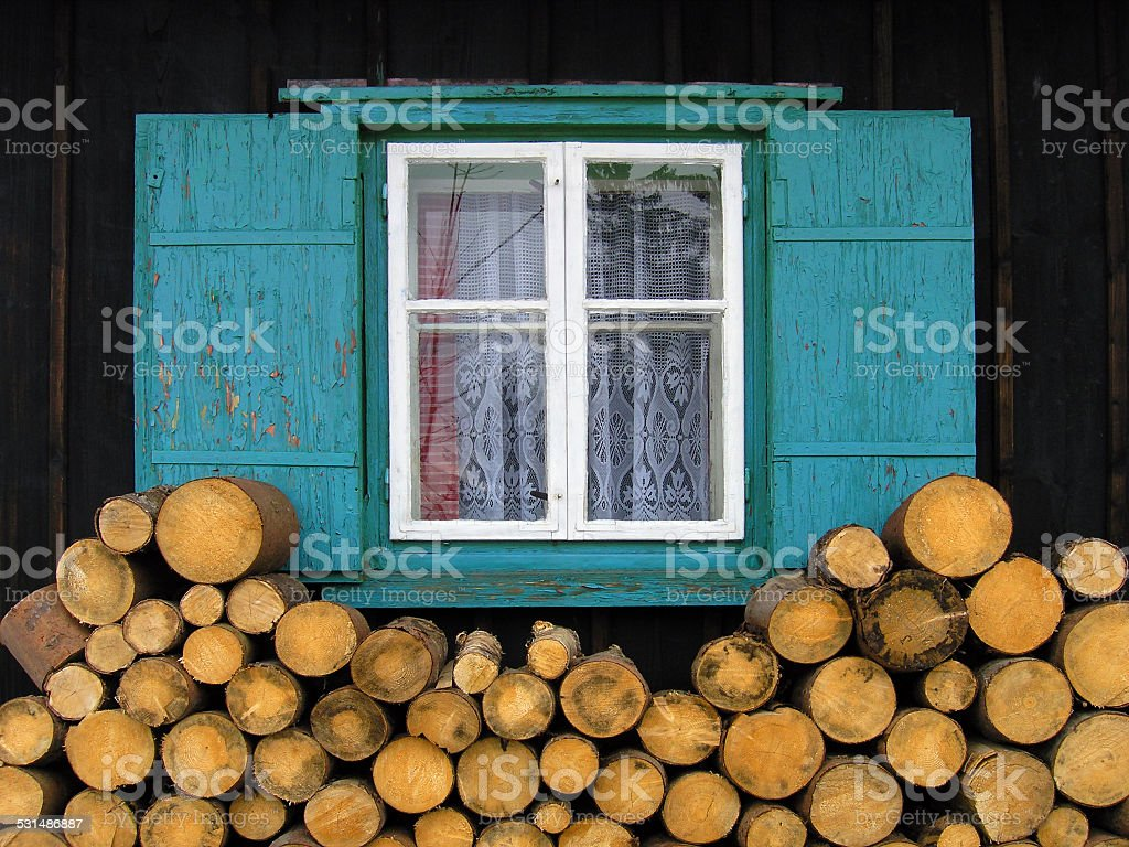 Window between logs of wood stock photo
