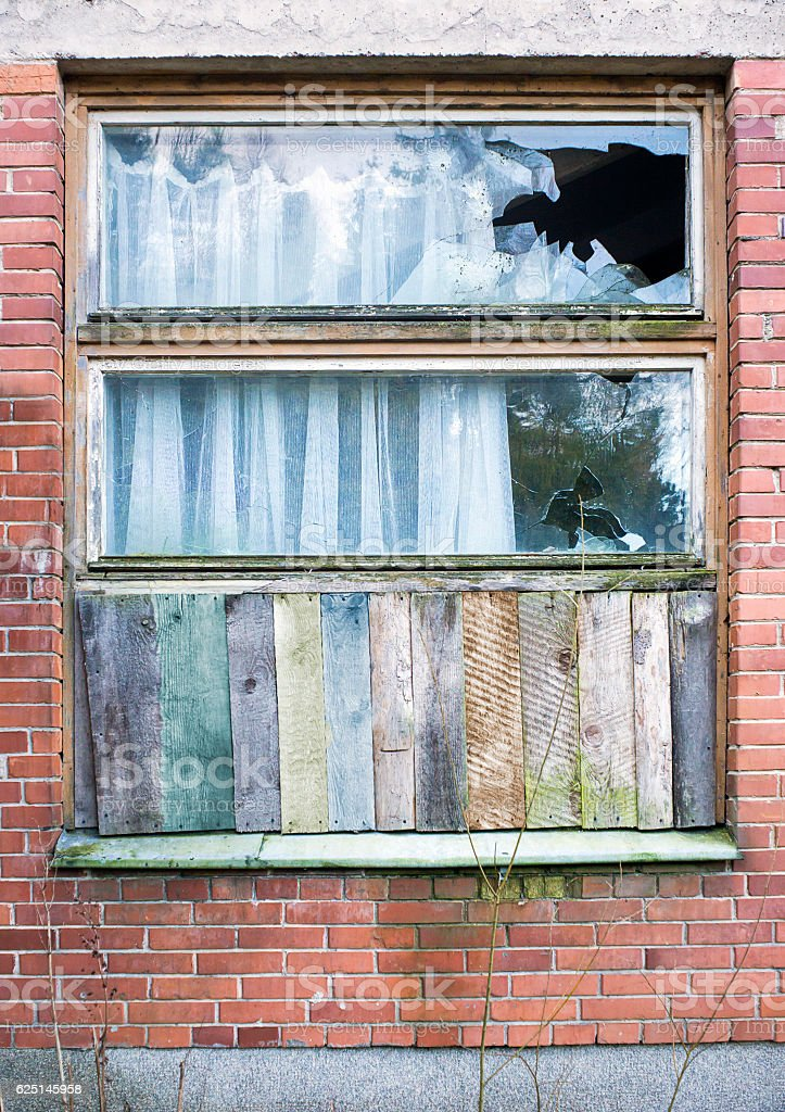 Window boarded up by wooden panels stock photo