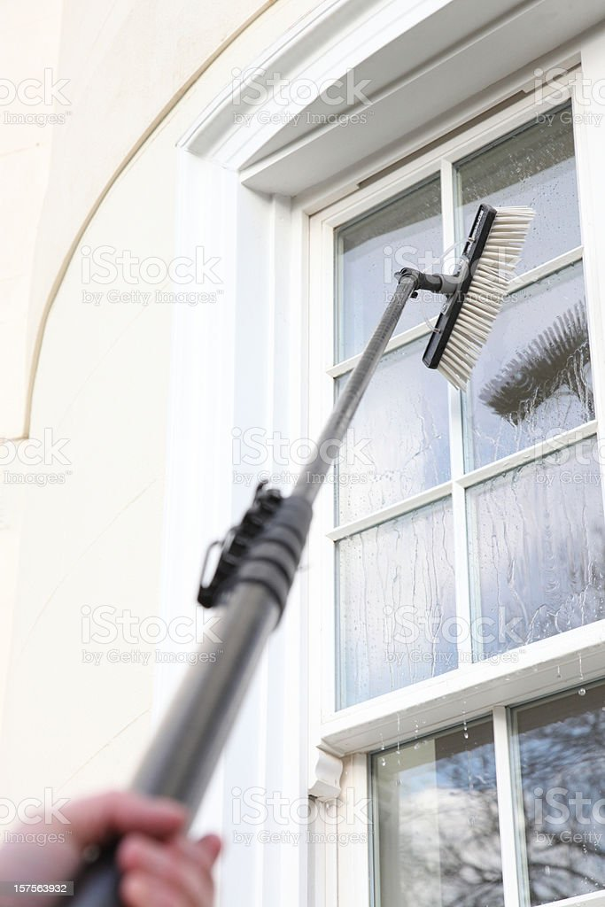 Window cleaner using the water fed pole system royalty-free stock photo
