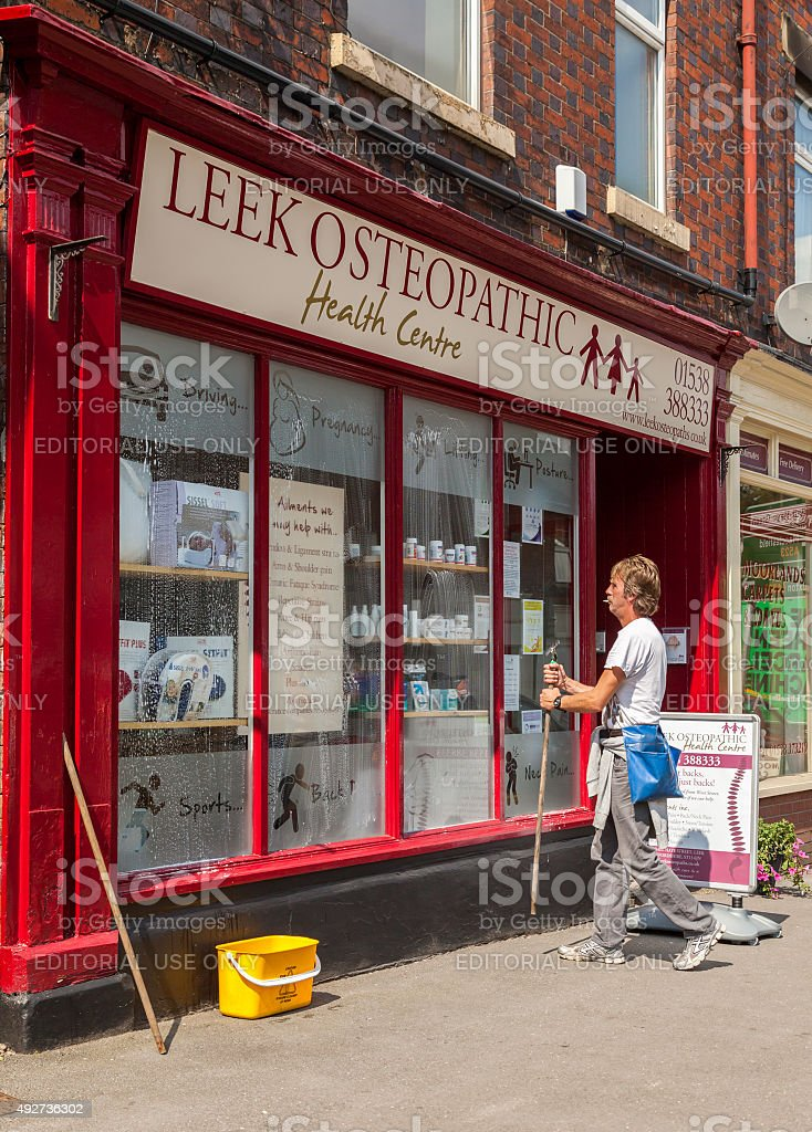 Window cleaner washing commercial windows in market town Leek, Staffordshire. stock photo