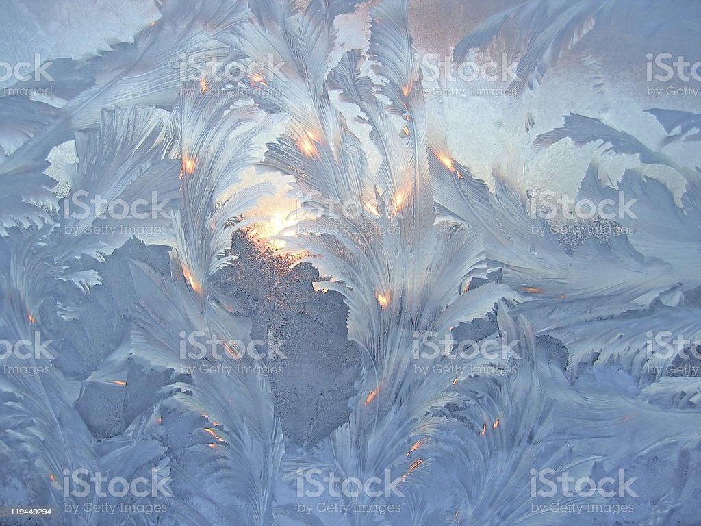 Window covered in frost with sunlight shining through royalty-free stock photo