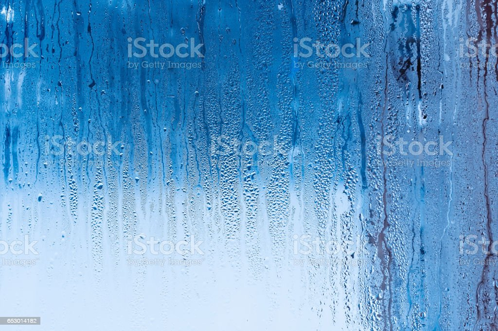 Window glass with condensation, strong, high humidity in the room, large water droplets flow down the , cold tone, natural  drops on stock photo