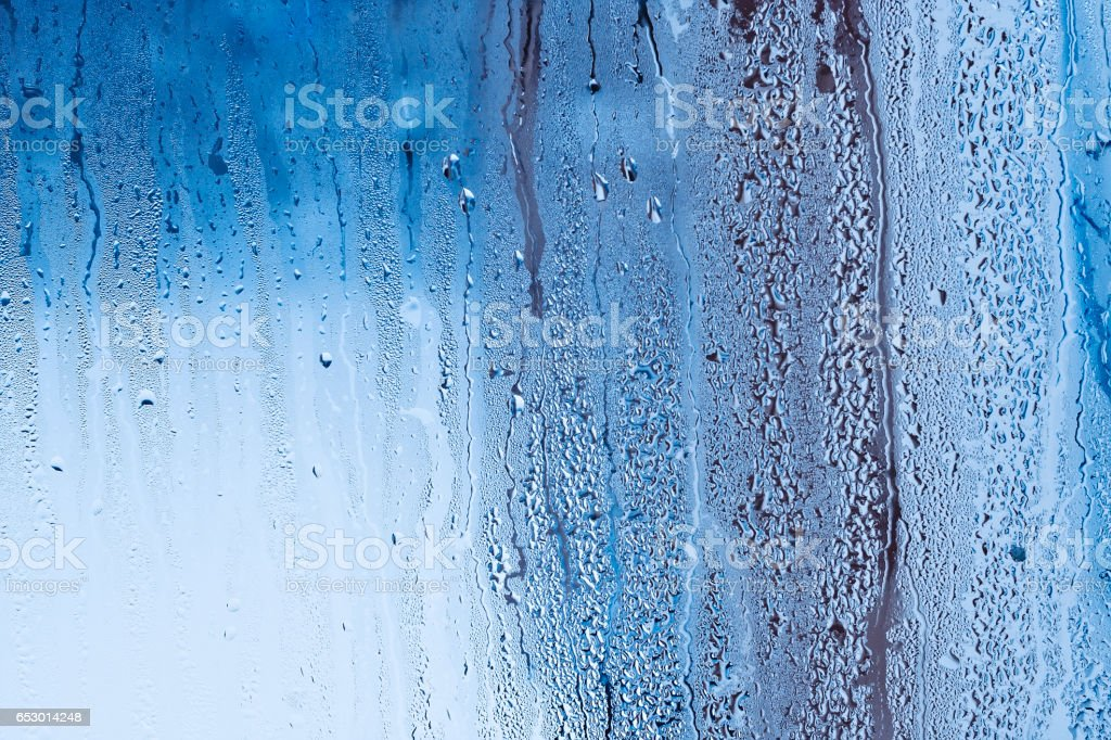 Window glass with condensation, strong, high humidity in the room, large water droplets flow down the window, cold tone, natural water drops on window glass stock photo