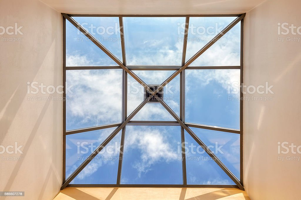 Window in a ceiling with blue sky stock photo