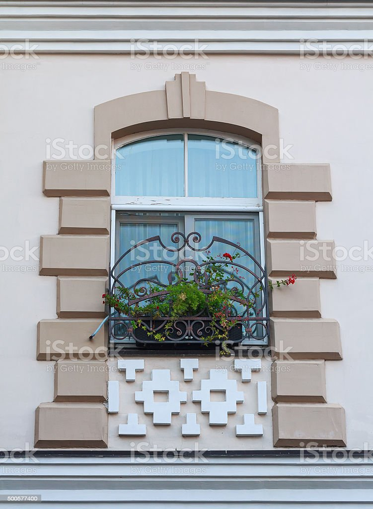 Window in a classic style and a box of flowers. Architecture stock photo