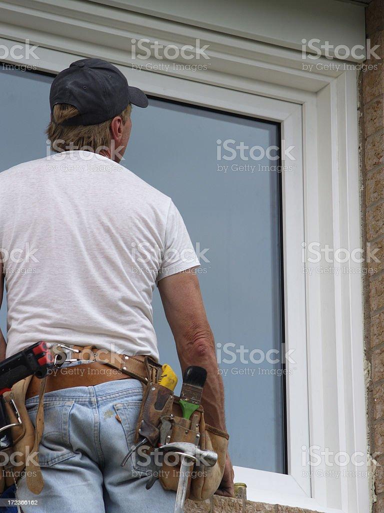 window installer with tool belt installing window royalty-free stock photo