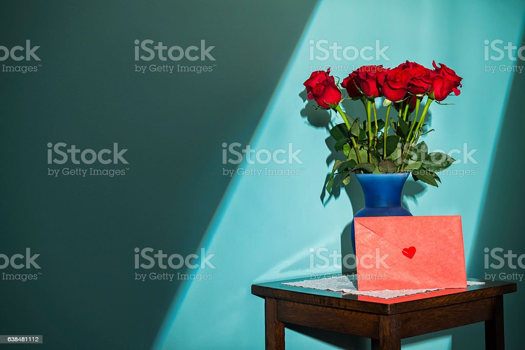Window light shining on a dozen red roses and card stock photo