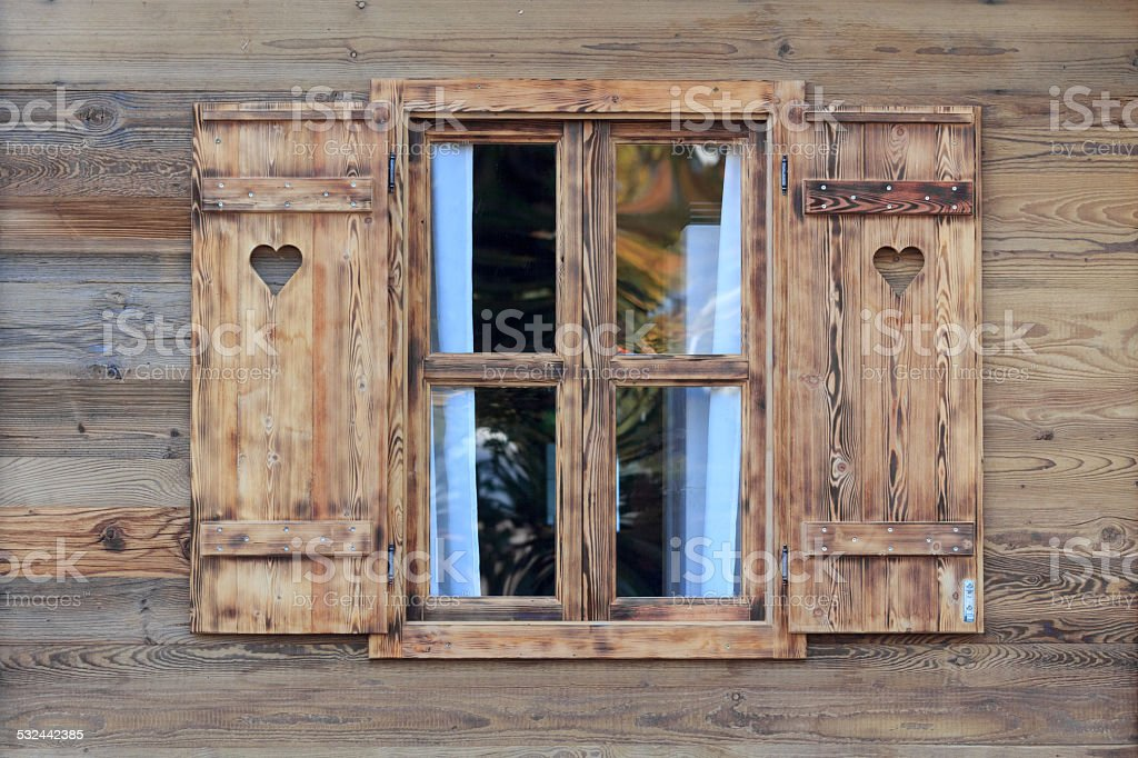 Window of a wooden hut with hearts in the blinds stock photo