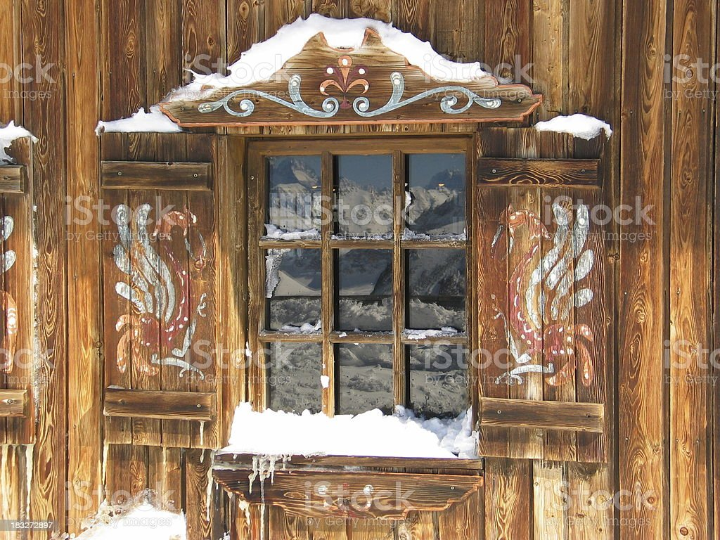 Window of a wooden snow hut with white landscape reflected stock photo