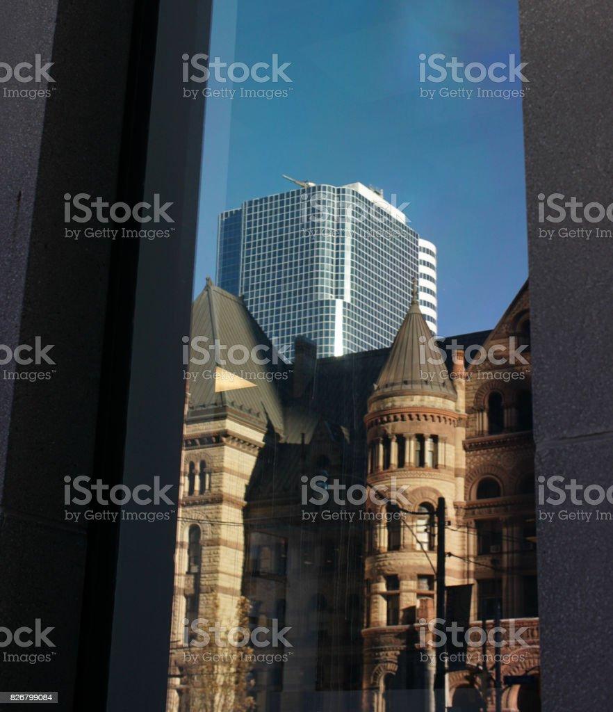 window on skyscraper reflecting old architecture stock photo