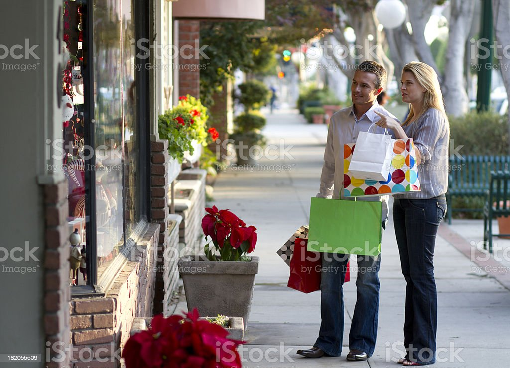Window shopping young adult couple carrying bags stock photo
