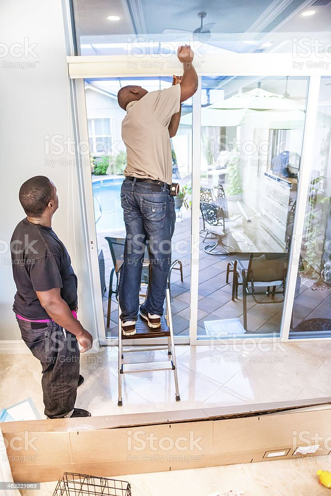 Window treatment being put up on sliding glass door royalty-free stock photo