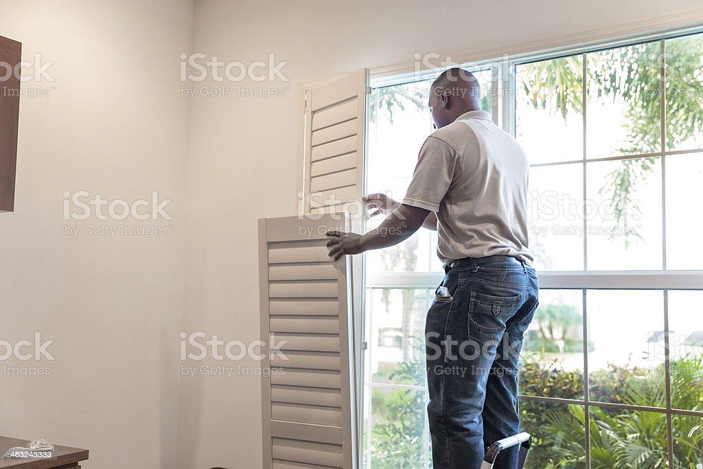 Window treatment installer installs wooden shutters royalty-free stock photo