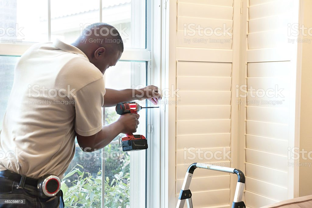 Window treatment installer installs wooden shutters stock photo