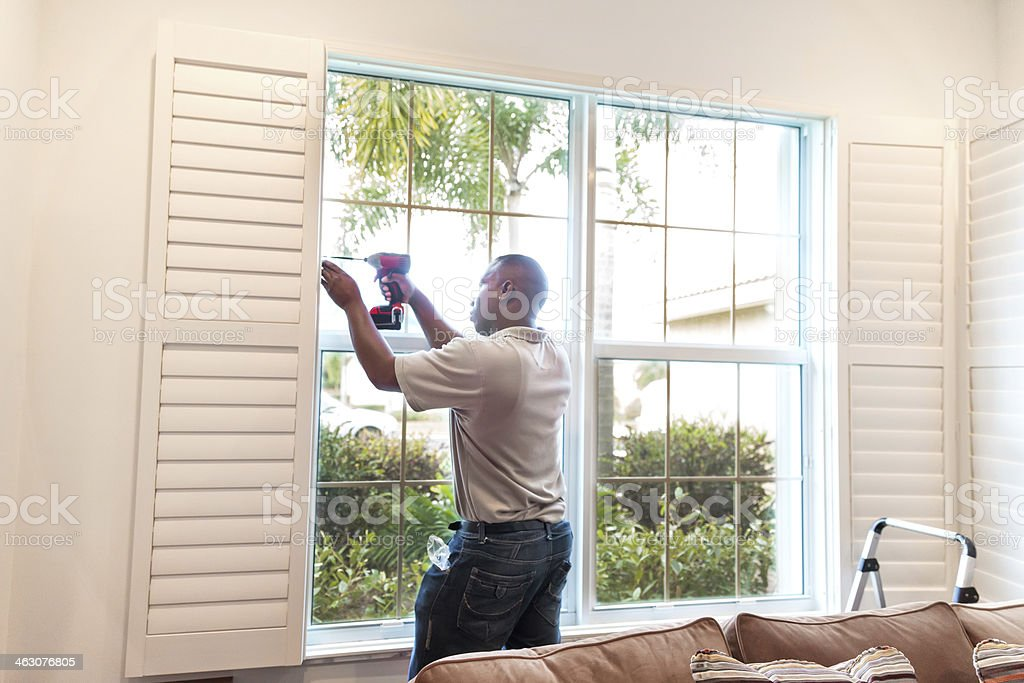 Window treatment installer installs wooden shutters  RM royalty-free stock photo