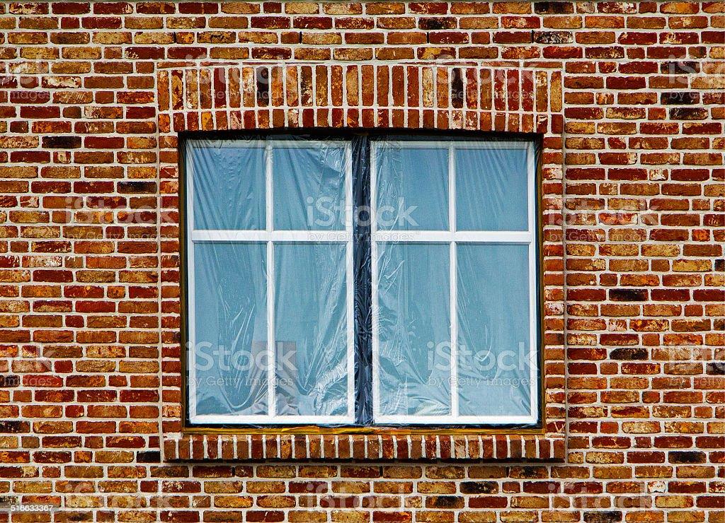 Window under the plastic film in brick wall stock photo