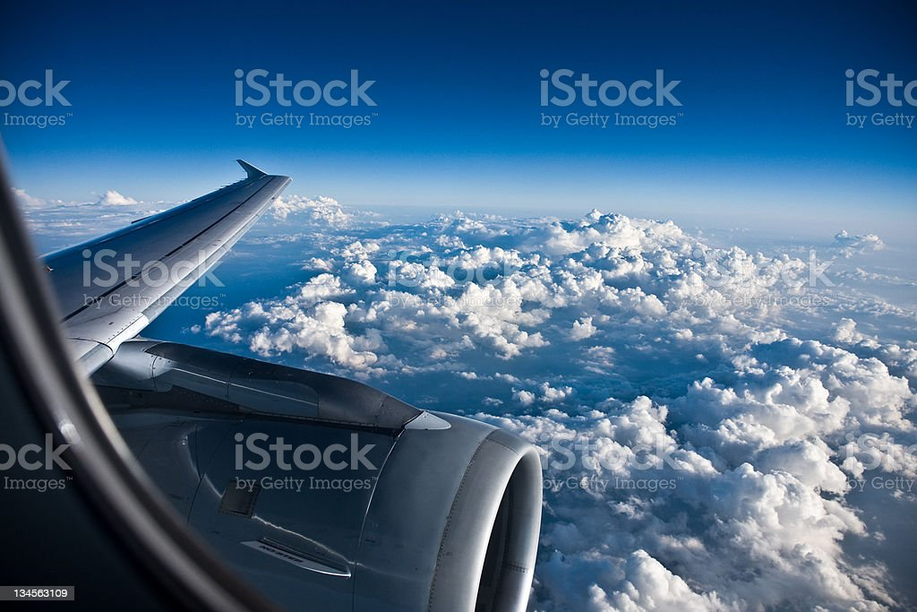 Window view of a planes wing above a billowy clouded sky royalty-free stock photo