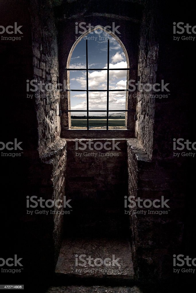 Window with a grid and sky in a castle stock photo