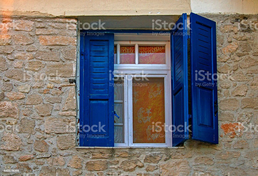 window with blue shutters stock photo