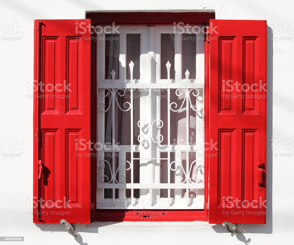 Window with grille and red shutters stock photo