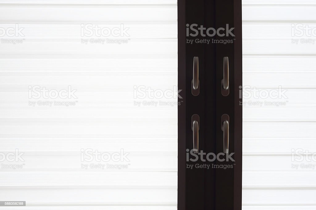 Window with latticed jalousie and doubled handles. Minimalistic interior detail. stock photo
