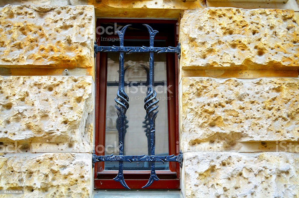 window with metal bars on street level stock photo