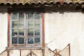 Window with shattered glass, ruined adobe house.