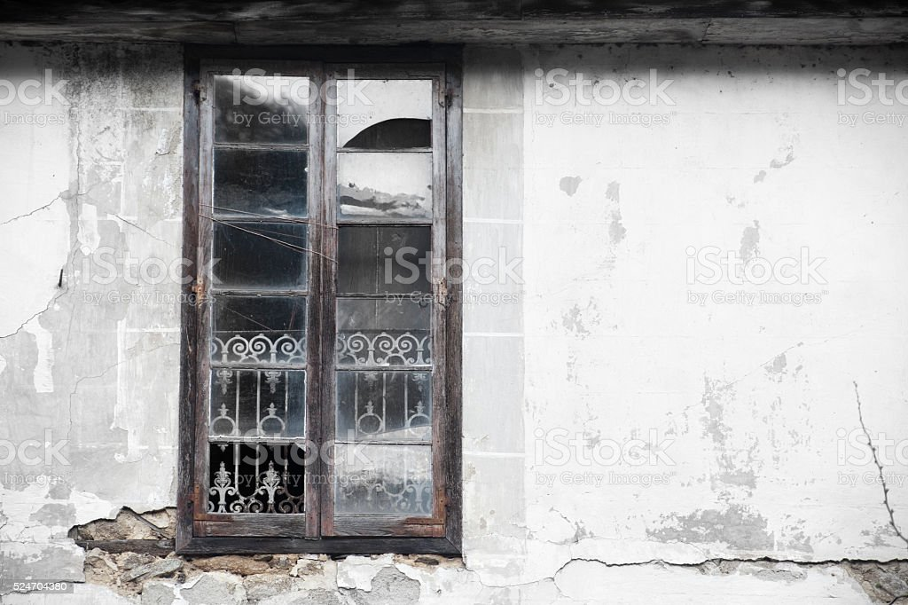 Window with shattered glass, ruined stone house. stock photo