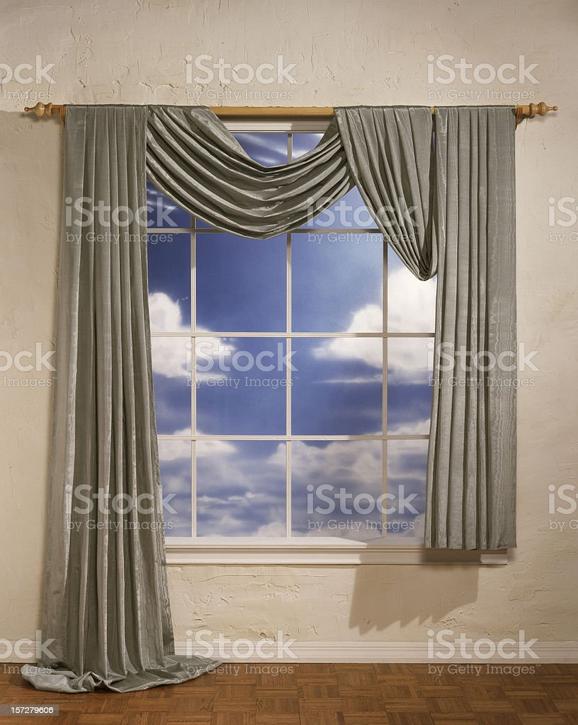 Window with uneven drapes showing a cloudy day royalty-free stock photo