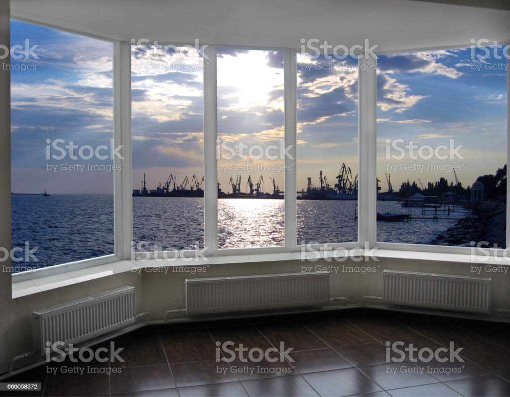 window with view of evening sea port docks and cranes stock photo