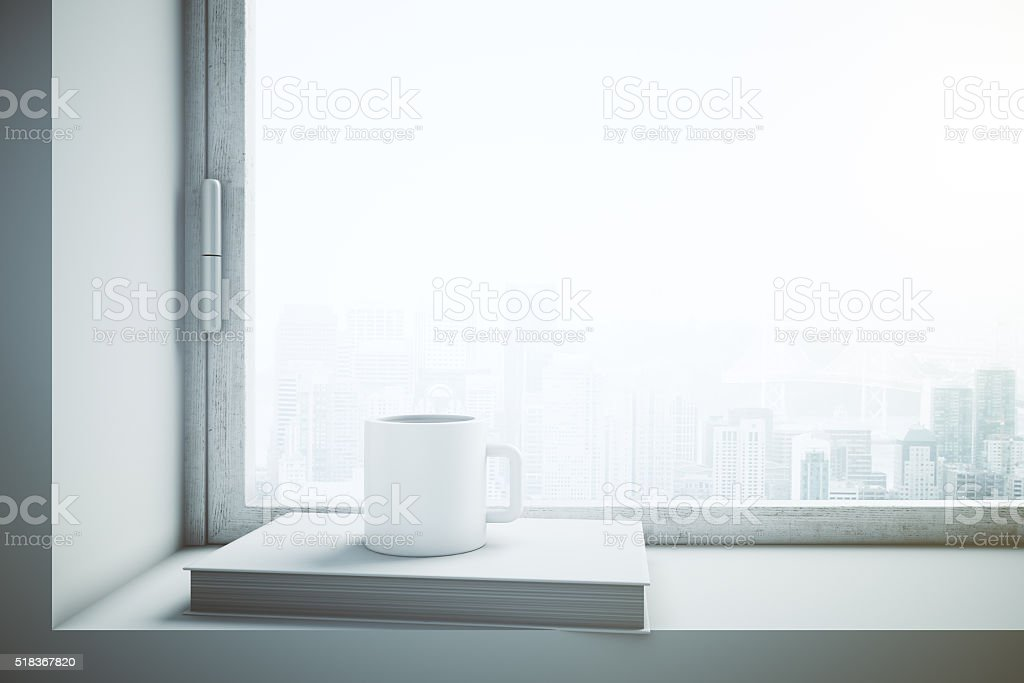 Window with white coffee cup and book stock photo