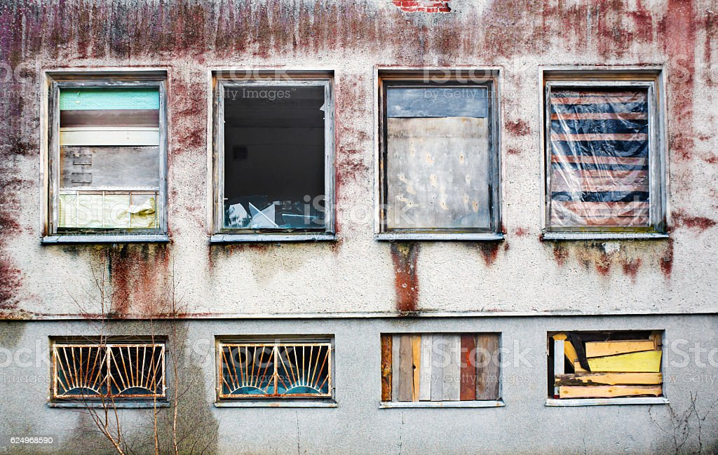 Windows boarded up by wooden panels in an old house stock photo