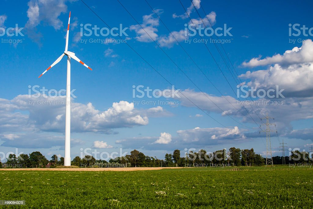 Windrad hinter Hochspannungsleitung stock photo
