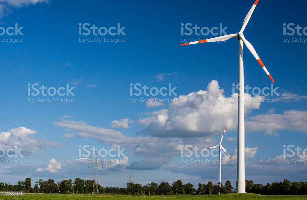 Windrad neben Hochspannungsleitung stock photo